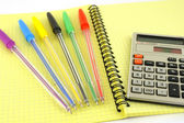 Old calculator and color pens on the yellow writing-book — Stock Photo