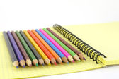 Color pencils on the yellow writing-book — Stock Photo