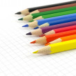 Color pencils on the checked paper of notepad — Stock Photo