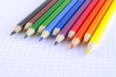 Color pencils on the checked paper of notepad — Foto de Stock