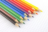 Color pencils on the checked paper — Stockfoto