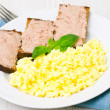 Breakfast with scrambled eggs and slice of toasted bread pate — Stock Photo
