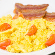 Scrambled eggs with tomatoes and bacon — Stock Photo