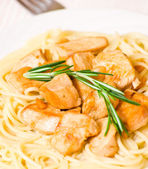 Sliced fried chicken fillet with garlic and rosemary. garnish spaghetti — Stock Photo