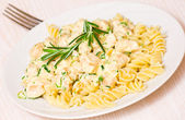 Sliced fried chicken fillet with garlic and rosemary in a creamy sauce. with fusilli pasta — Stock Photo