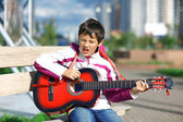 Music student playing the guitar outdoors — Stock Photo