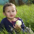 Boy with apple in green grass — Stock Photo