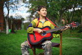 Young boy playing the guitar and sing outdoors — Stock Photo