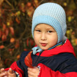 Little boy relaxing in autumn park — Stock Photo