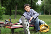 Young boy with bicycle relaxing outdoors — Stock Photo