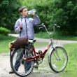 Royalty-Free Stock Photo: Young boy with bicycle with drinking clear water