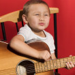 Stock Photo: Little music student playing the guitar