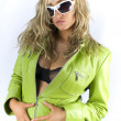Blondie in green jacket, short jeans skirt and sun glasses posing in studio — Foto de Stock