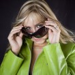 Blonde in green leather jacket and glasses — Stock Photo