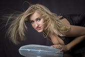 Blond posing and fan blows in her face — Stock Photo