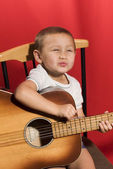 Little music student playing the guitar — Stock Photo