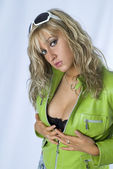 Blondie in green jacket and sun glasses posing in studio and holding her breast — Stock Photo