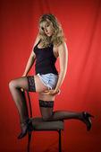 Blondie i svart stokings poserar på stol över röda bakcground — Stockfoto