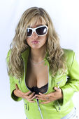 Blondie in sun glasses and green jacket posing in studio and holding her breast — Stock Photo