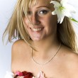 Cute blondie with naked shoulders laying covered with rose petals and lily — Stock Photo #15826911
