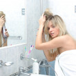 Woman in the bathroom at mirror — Stock Photo #15827591