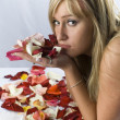 Cute blondie with naked shoulders laying covered with rose petals — Стоковая фотография