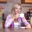 Woman sniffing the scent cup of hot drink, breakfast in the kitc — Stockfoto