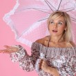 Stock Photo: Woman under umbrella against pink