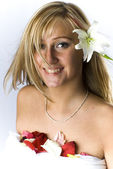 Cute blondie with naked shoulders laying covered with rose petals and lily — Stock Photo