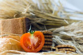 Wheat ears, Fresh red tomato, cookies and bread bagels on wooden table — Stock Photo