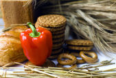 Wheat ears, Fresh red pepper, cookies and bread bagels on wooden table — Stock Photo