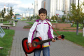 Boy playing the guitar outdoors — Stock Photo
