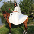 Bride horseback at brown horse - Stock Photo