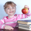 Little girl with apple and books — Stock Photo