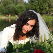 Bride with a rose near the lake — Stock Photo