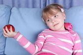 Surprised little girl with apple in sofa — Stok fotoğraf