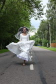 Runaway bride on a road — Stock Photo