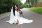 Bride with a rose sitting on a road — Stock Photo
