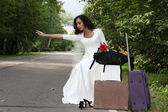 Runaway bride hitch-hiking on a road — Stock Photo