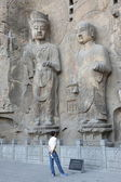 Man looking on old sculpture. Dragons Gate Grottoes — Stock Photo