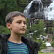 Teenage boy near the Tvindefossen Waterfall in summer sunny day, Norway — Stock Photo