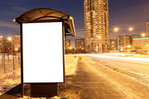 Blank sign at bus stop at evening in city — 图库照片