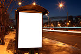Blank sign at bus stop in evening city — 图库照片