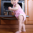 Child 1 year old in the kitchen cooking breakfast — Stock Photo