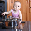Child 1 year old in the kitchen cooking breakfast — Stock Photo #41669301
