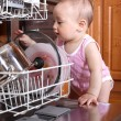 Child 1 year old in the kitchen at dishwasher — Stock Photo #41669355