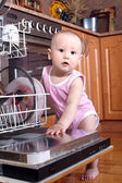 Child 1 year old in the kitchen at dishwasher — Stock Photo