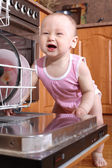 Funny child 1 year old in the kitchen at dishwasher — Stock Photo