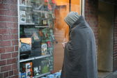 Homeless man stands in front of shop window — Stock Photo