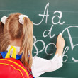Schoolchild writting on blackboard — Photo #12070052